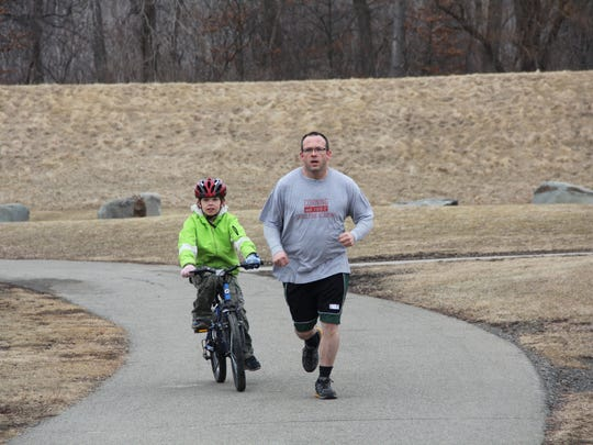 Dwayne Harshberger of Elmira jogs Tuesday morning at Eldridge Park, accompanied by his son Heath.