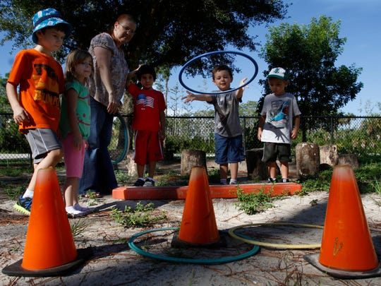 Jack Casey, center, tosses a small hula hoop towards an orange cone at the Family Resource Center at FGCU Wednesday.