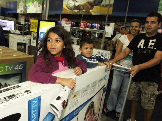 Hutchson Santos, his wife Agvida, and their children Caun,5, and Luanna,7, pick up a big flat screen TV at Best Buy taking advantage of the sale on Black Friday, 11/25/11.
