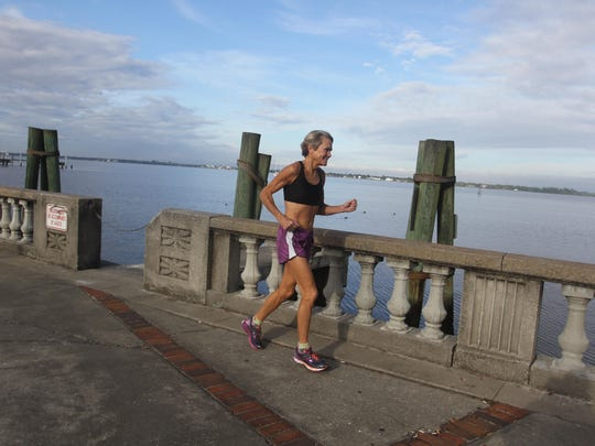 Karen Miles, one of the top 60-64 year old runners in the country, runs along thru Centennial Park as she prepares for the Naples Half-Marathon on Sunday.