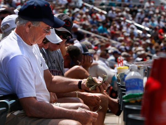 Part-time Florida resident and Boston Red Sox fan Bob Cicale counts dollar bills during the Red Sox-Twins baseball game Wednesday in Fort Myers.