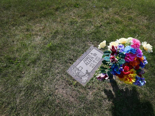 A small vase of flowers sits beside the grave of James Allen III in Crown Hill cemetery Wednesday, Oct. 2, 2014. Allen was killed in a shootout in August 2012.