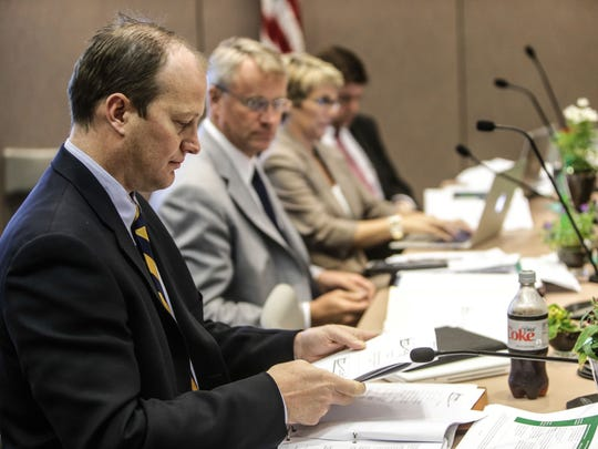 Indiana State Board of Education member Gordon Hendry looks over materials during a May 13, 2014, meeting at the Indiana Government Center, Indianapolis.