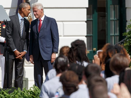 President Barack Obama talks with former President Bill Clinton during a ceremony on the South Lawn of the White House in Washington, Friday, Sept, 12, 2014, to mark the 20th anniversary of the AmeriCorps national service program. President Barack Obama and former President Bill Clinton joined forces Friday to mark the 20th anniversary of the AmeriCorps national service program, heralding the impact volunteering can have on both individuals and the nation.
