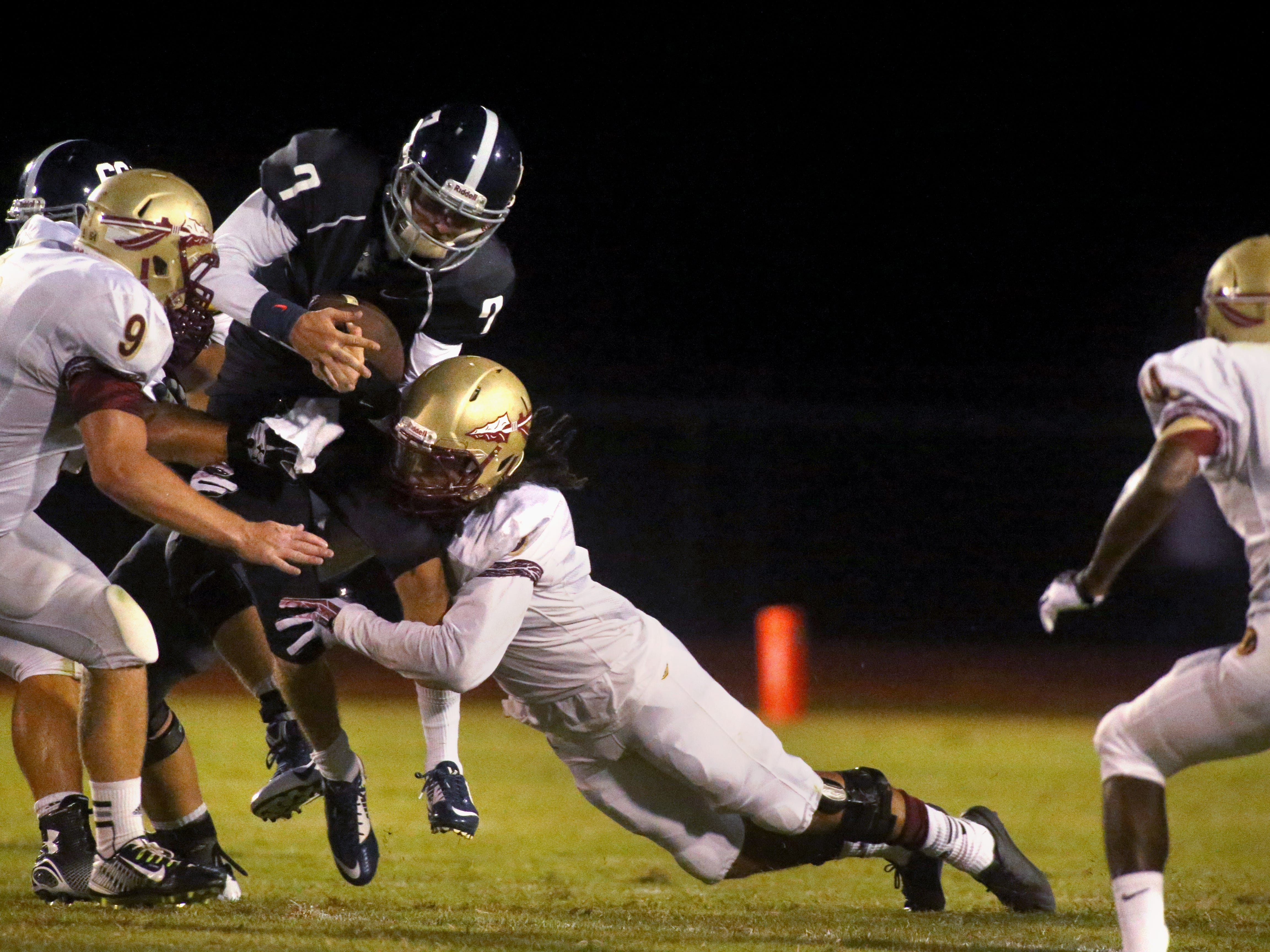 Siegel's quarterback Jordan Middleton runs the ball as he is tackled by Riverdale's Ben Wells and Austin McGrone during the week zero game at Siegel, on Friday, August 22, 2014.