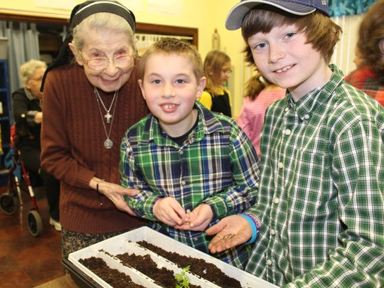 Sister Connie, left, with Lourdes students Ethan Olson and Caden McKone exchanging letters and planting herbs.