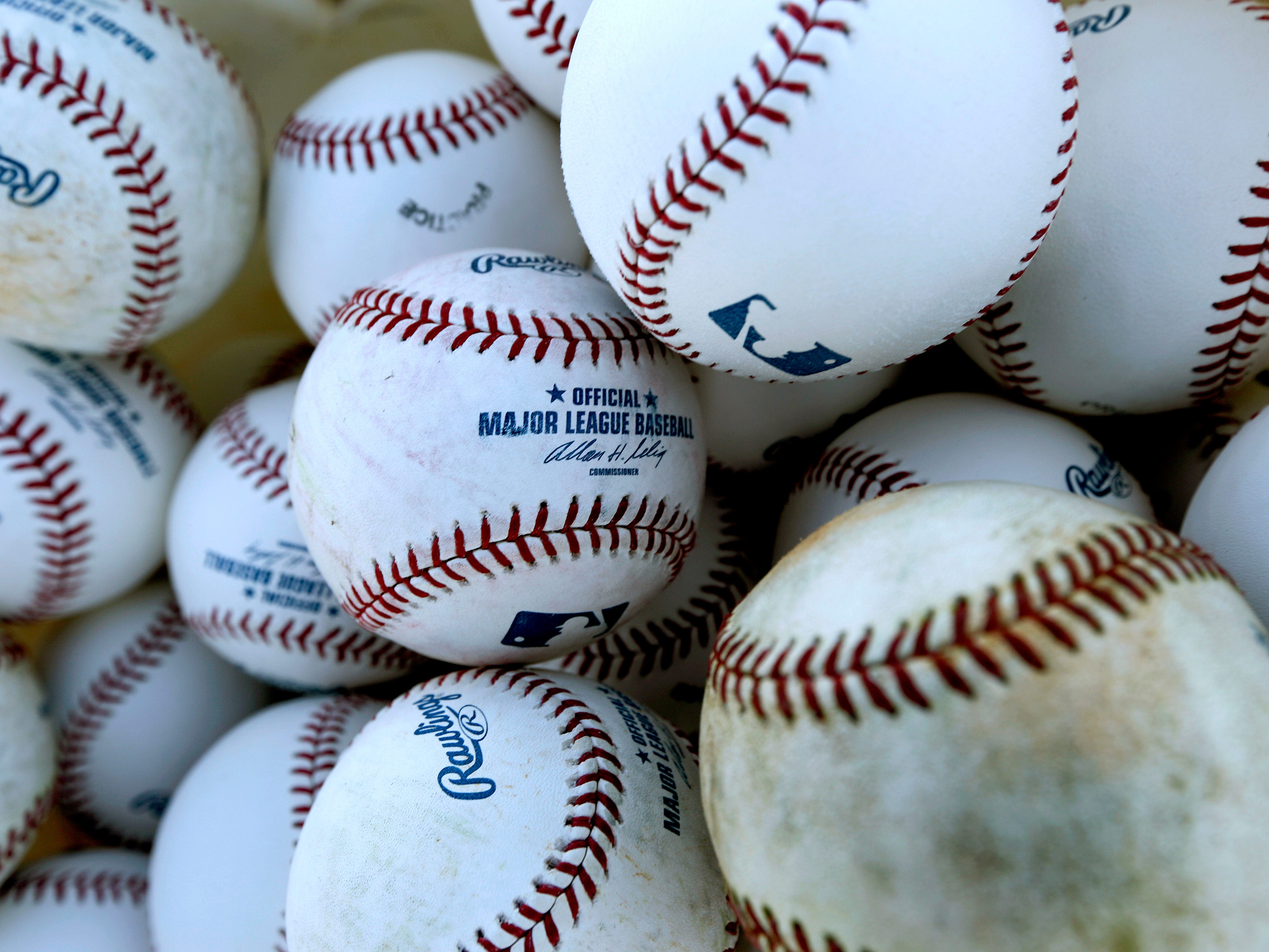 Baseballs sit in a bucket before the official start of spring training baseball at the St. Louis Cardinals training facility, Monday, Feb. 11, 2013, in Jupiter, Fla. (AP Photo/Julio Cortez)