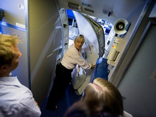 In this Sept. 10, 2014 photo, British Airways flight safety instructor Diane Pashley teaches participants how to open one of the aircraft doors onboard a cabin simulator during a flight safety course at the airline's Cranebank training facility, near Heathrow airport in London. The half-day safety course, now open to frequent fliers willing to pay $265, encourages passengers to be aware of their surroundings and familiarize themselves with what happens in an emergency. (AP Photo/Matt Dunham)