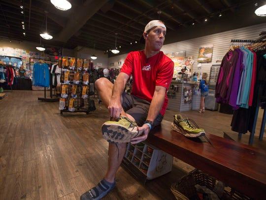 Mark Cosmas (L) puts on his Hoka running shoes before