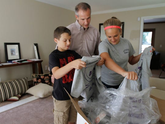 Justin, Brian and Megan Norton sort through the team Hugs4Mom T-shirts in preparation for the Walk to End Alzheimer's in 2014.