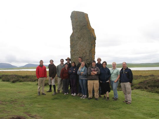 Students from Willamette University traveled to the Orkney Islands north of Scotland for a summer field experience at the Ness of Brodgar. They are posing with the Standing Stone at the Ring of Brodgar.
