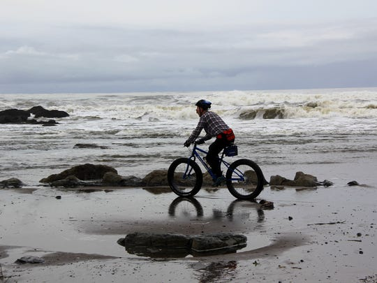 West Salem resident Craig Wojcik rides his fat bike on the Oregon Coast beach in Lincoln City between Taft and Roads End State Park.