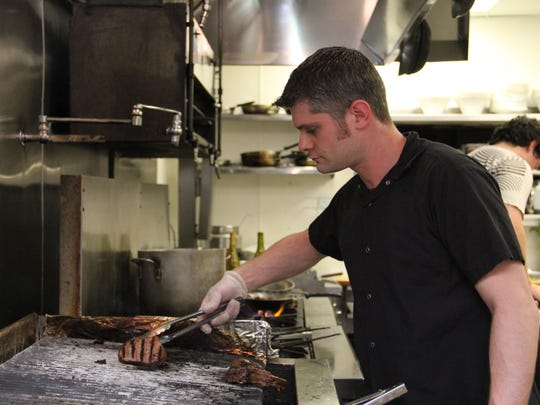 Ryan Hall grills a steak and lamb chops at Delaney Madison Grill in Keizer on Thursday, March 5, 2015.