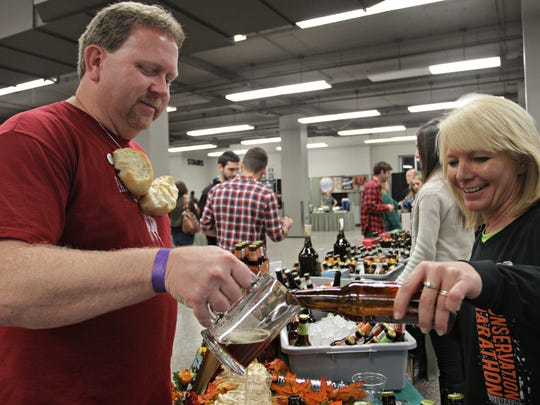 Volunteer Penny Richards pours a sample for Bret McGowne during a previous Ozarks Beerfest at the Springfield Expo Center.