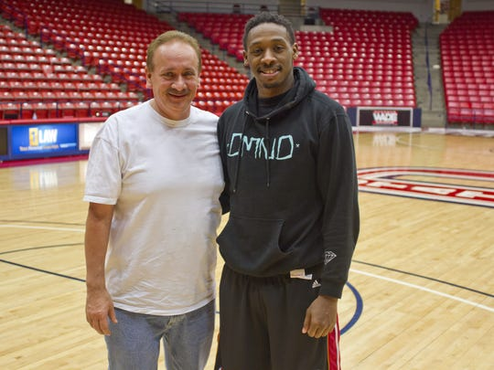 Dixie State guard DeQuan Thompson poses with adopted dad Darryl Littlefield after Dixie's win over Chaminade Thursday, Feb. 12, 2015.