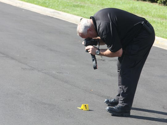 Two people were hospitalized, one with gunshot wounds, following a suspected robbery in the North Monroe Street area. Police roped off the Super 8 motel and La Quinta Inn on North Monroe Street on Wednesday afternoon. An investigator takes photographs of evidence found on scene.