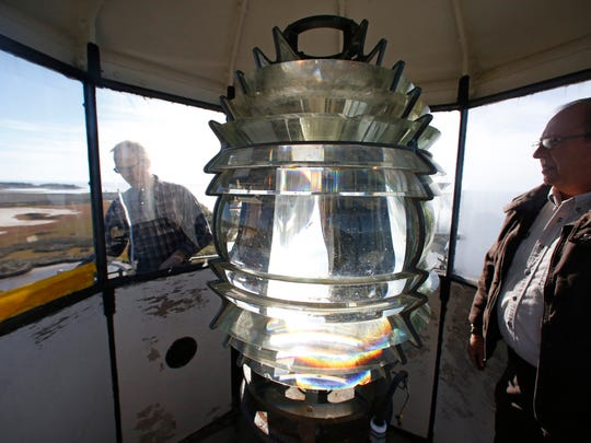Chris Weber, preservation coordinator with St. Marks National Wildlife Refuge, inspects the Fresnel lens in the St. Marks Lighthouse before crews began the removal process.