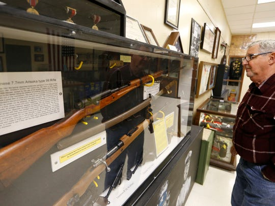 Tony Minichiello, president of the Camp Gordon Johnston Museum, looks over a case of rifles that were donated to the WWII memorabilia collection at the museum. Most everything housed within the museum in Carrabelle is donated by military veterans and their families.