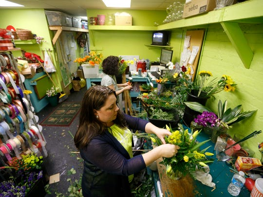 Roxie Singletary, owner of Elinor Doyle Florist, works with floral designer Aletha Young, top, on Monday to create the more than one hundred floral arrangements to be delivered to the Capitol building to start the legislative session.