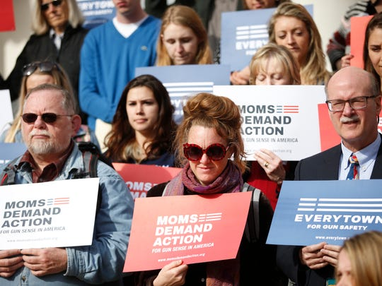 Protestors hold signs on the Capitol steps Monday against the passing of new legislation that would allow concealed carry weapons on Florida University campuses.