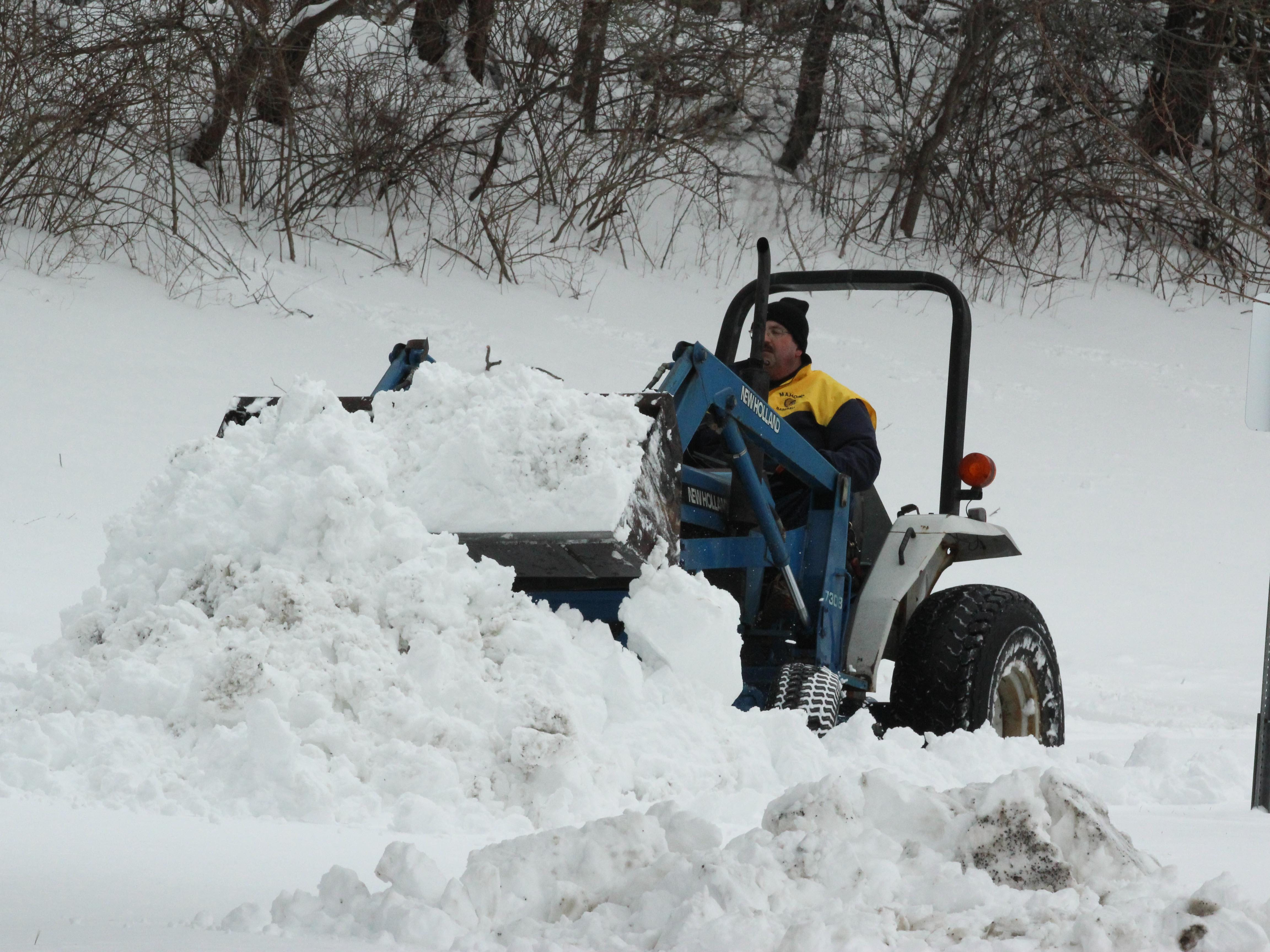 A plow clears snow from parking lots during a snow day in Mahopac, N.Y.