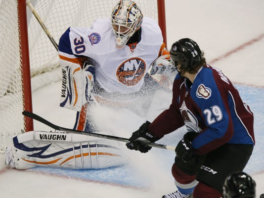 New York Islanders goalie Chad Johnson, back, deflects shot off the stick of Colorado Avalanche center Nathan MacKinnon in the third period of the Avalanche's 5-0 victory in an NHL hockey game in Denver on Thursday, Oct. 30, 2014. (AP Photo/David Zalubowski)