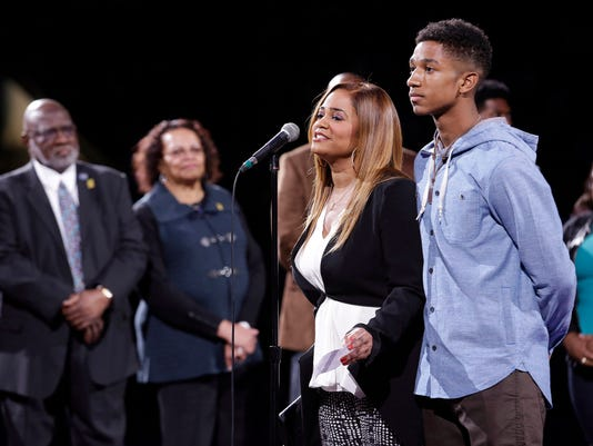 Kendall Phills, widow of former Charlotte Hornet Bobby Phills stands with her son Trey Phills, to thank the Charlotte fans for retiring her deceased husband's jersey during halftime of an NBA basketball game in Charlotte, N.C., Saturday, Nov. 1, 2014. (AP Photo/Bob Leverone)