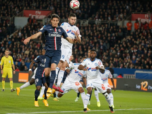 Paris Saint Germain's Edinson Cavani, left, challenge to head the ball with Marseille's Andre-Pierre Gignac during their French League One soccer match match between Paris Saint Germain and Marseille at Parc des Princes stadium in Paris, France, Sunday, Nov. 9, 2014. (AP Photo/Francois Mori)