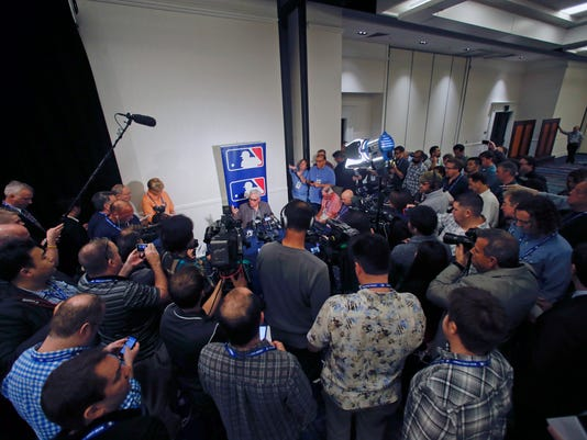 Chicago Cubs manager Joe Maddon draws the largest crowd of media covering the Major League Baseball winter meetings Tuesday, Dec. 9, 2014, in San Diego. (AP Photo/Lenny Ignelzi)