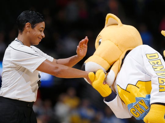 Referee Violet Palmer, left, receives a kiss on the hand from Denver Nuggets mascot Rocky the mountain lion just before tipoff as the Nuggets host the Orlando Magic in the first quarter of an NBA basketball game Wednesday, Jan. 7, 2015, in Denver. (AP Photo/David Zalubowski)