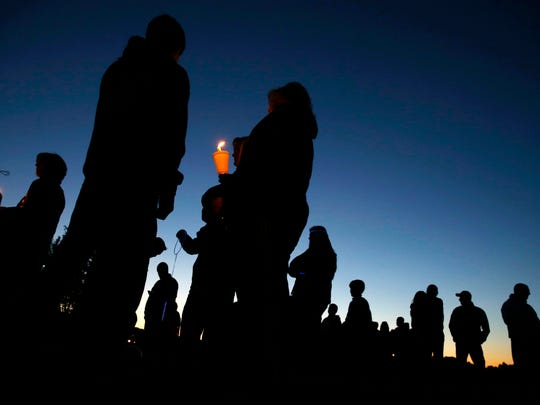 People hold candles as they gather for an anti-bullying rally Oct. 12 in Sayreville, where hazing allegations led to the high school football season being canceled.