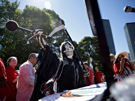 A person dressed as the grim reaper hits a gong in protest along Las Vegas Boulevard, Wednesday, Sept. 24, 2014, in Las Vegas. Nurses in town for the California Nurses Association and National Nurses Organizing Committee convention protested on the Strip because they say U.S. hospitals aren't ready for an Ebola outbreak. (AP Photo/John Locher)