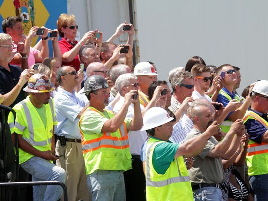 Workers at the I-495 bridge site take pictures of President Barack Obama as delivers remarks at the Port of Wilmington.