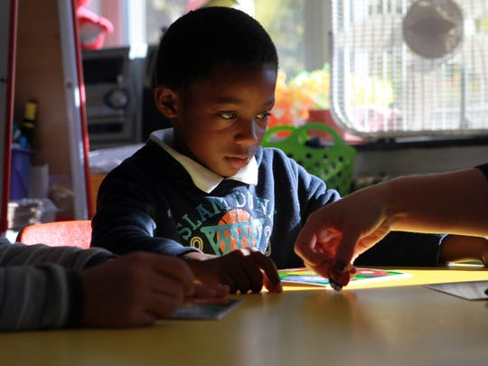 Six-year-old Jayvon Minus-Whye works on sounding out vowels with first grader teacher Emilie Bullins at Stubbs Elementary School.