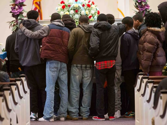 Police attribute much of the violence among Wilmington's young people in recent years to smaller-scale instances of disrespect, which escalate into gunfire. Above, friends gather around the open casket of William Rollins, killed in an ambush in late January. See story A10.