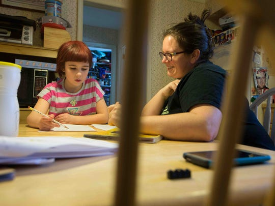 Jackie Kook works on a reading exercise with her daughter Caitlin, 9. Kook, a Christina School District teacher, is opting to take Caitlin out of state standardized testing.