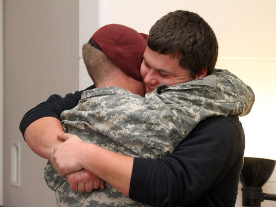 U.S. Army Specialist Roel Martinez embraces his stepbrother, Wes Harvey, after surprising him Friday in Harvey's class at Mid-East Career and Technology Center in Zanesville. Martinez recently returned from a nine-month deployment in Afghanistan, his first, and will return to service in a month.