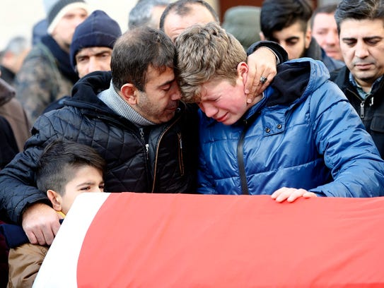 Relatives mourn at the coffin during the funeral of