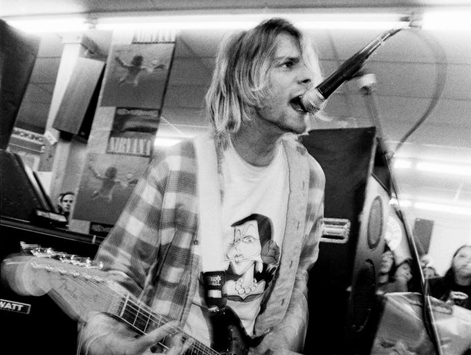 "Twenty years after his death, Kurt Cobain's musical legacy lives on. Here's a look back at the icon over the years. Here, he plays his Fender Jaguar guitar during Nirvana's ""Nevermind"" release party on Sept. 16, 1991."