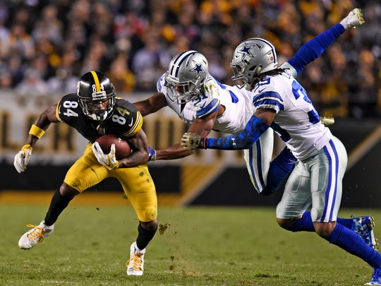 Pittsburgh Steelers wide receiver Antonio Brown (84) is tackled by Dallas Cowboys free safety Byron Jones (31) and Brandon Carr (39) during the second half of an NFL football game in Pittsburgh, Sunday, Nov. 13, 2016.