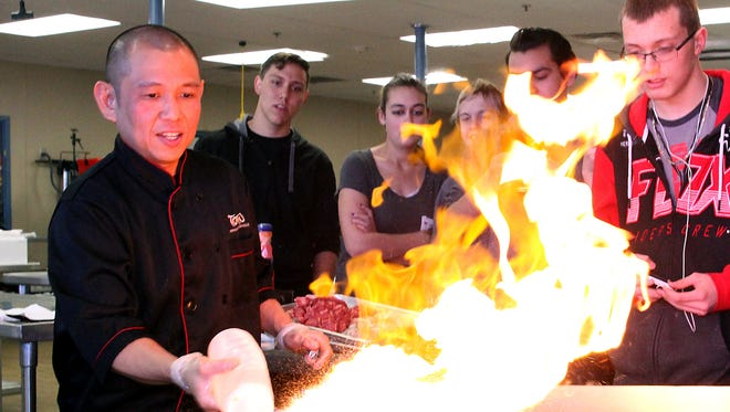 Chef Opi Sinyal of Tomo Japanese Sushi & Steak House does a cooking demonstration on a hibachi grill for students in Eddie Gurrola's culinary essentials class on Thursday at the Career and Technology Education Center in Farmington.