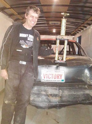 "Pulaski's Larry ""Junior"" Karcz poses with his trophy after winning the IMCA stock car feature May 16 at 141 Speedway in Francis Creek."