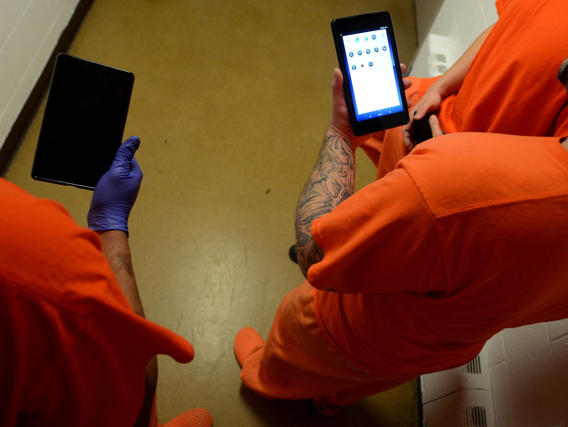 A group of inmates hold their tablets in their hands