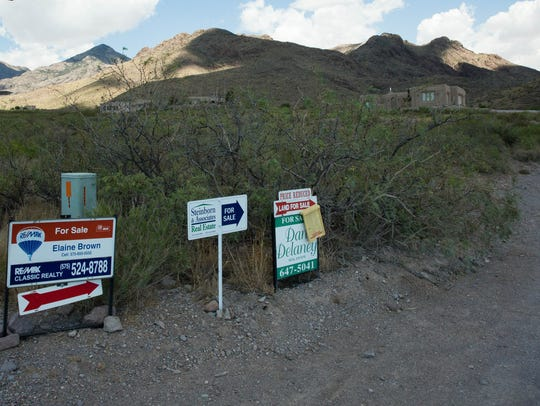 For sale signs sit along one of the many unpaved roads