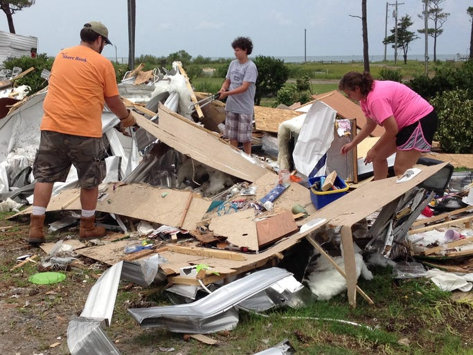 Volunteers removed debris and load it into a waiting dumpster during the Cherrystone Campground cleanup day. A tornado struck the campground on July 24, killing two and injuring 36.