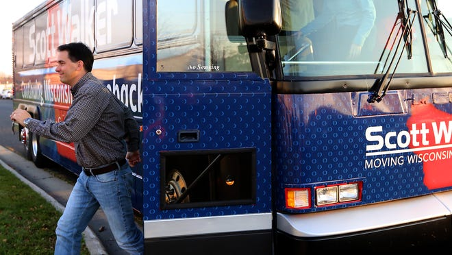 Wisconsin Gov. Scott Walker exits his campaign bus during a campaign tour stop at Vortex Optics on Monday in Middleton.
