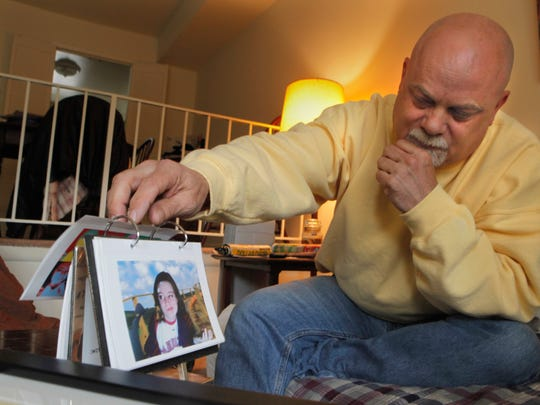 Dave Markham sits in his Fairfield living room with photos of his daughter, Katelyn Markham.