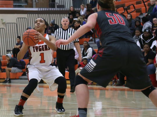Mansfield Senior's Talayzha Catchings shoots for the hoop in front of Shelby's Bailey Walter at Mansfield Senior High School on Tuesday evening.