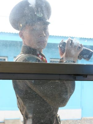 An unimpressed North Korean Border Guard watches Al Cooper through a  fly-specked glass window in De-militarized Zone.