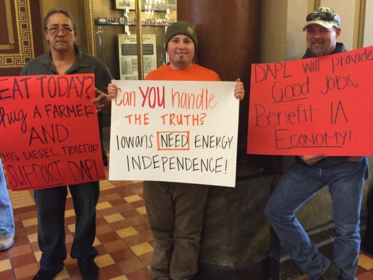 Construction workers supporting the proposed Bakken pipeline held signs at the Iowa Capitol Thursday while pipeline foes conducted a rally in the Rotunda.
